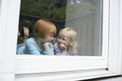 Cute Little Sisters Lying In Front Of Glass Window Royalty Free Stock Images