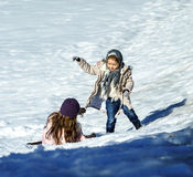 Cute little sisters playing in snow, sunny day Royalty Free Stock Photography