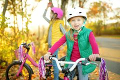 Cute little sisters riding bikes in a city park on sunny autumn day. Active family leisure with kids. Children wearing safety helmet while riding a bicycle royalty free stock image