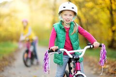 Cute little sisters riding bikes in a city park on sunny autumn day. Active family leisure with kids. Children wearing safety helmet while riding a bicycle stock image