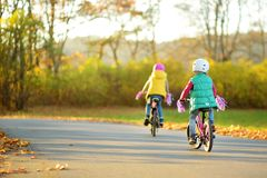 Cute little sisters riding bikes in a city park on sunny autumn day. Active family leisure with kids. Children wearing safety helmet while riding a bicycle royalty free stock images