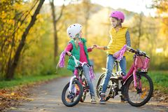 Cute little sisters riding bikes in a city park on sunny autumn day. Active family leisure with kids. Children wearing safety helmet while riding a bicycle stock images