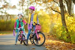 Cute little sisters riding bikes in a city park on sunny autumn day. Active family leisure with kids. Children wearing safety helmet while riding a bicycle royalty free stock photography