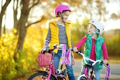 Cute little sisters riding bikes in a city park on sunny autumn day. Active family leisure with kids. Children wearing safety helmet while riding a bicycle stock photo