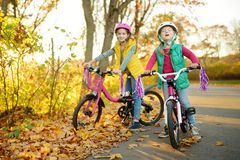 Cute little sisters riding bikes in a city park on sunny autumn day. Active family leisure with kids royalty free stock photos