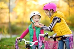 Cute little sisters riding bikes in a city park on sunny autumn day. Active family leisure with kids. Children wearing safety helmet while riding a bicycle stock photography