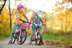 Cute little sisters riding bikes in a city park on sunny autumn day. Active family leisure with kids. Children wearing safety helmet while riding a bicycle royalty free stock photos