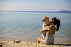 Cute little sisters sitting on a beach. At summer stock photography