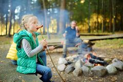 Cute little sisters and their father roasting hotdogs on sticks at bonfire. Children having fun at camp fire. Camping with kids in royalty free stock image