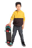 Cute little skater boy holding a skateboard. Full length portrait of a cute little skater boy holding a skateboard and looking at the camera isolated on white Stock Images