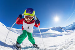 Cute little skier posing with poles at sunny day Royalty Free Stock Images