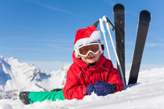 Cute little skier in Santa`s hat laying on snow Stock Images