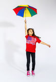 Cute little smiling afro-american girl jumping with colorful umb Stock Image