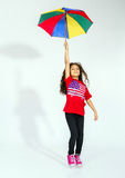Cute little smiling afro-american girl jumping with colorful umb Royalty Free Stock Photos