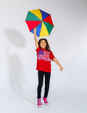 Cute little smiling afro-american girl jumping with colorful umb Royalty Free Stock Photography