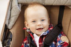 Cute little smiling baby in a baby carriage on the streets of th Stock Photography