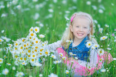 Cute little smiling baby girl in chamomile field Little blond child with wreath on head in chamomiles wearing jeans and pink skirt Stock Images