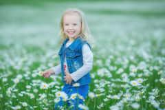 Cute little smiling baby girl in chamomile field Little blond child with wreath on head in chamomiles wearing jeans and pink skirt stock photo