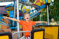 Cute little smiling boy riding a Carnival Carousel Stock Images