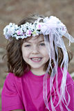 Cute little smiling gir with flowers in hairl. Beautiful little smiling girl with curly brown hair wearing a pink dress and flowers and ribbons  in her hair Royalty Free Stock Images
