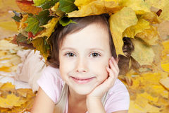 Cute little smiling girl in autumn leaves Stock Photo