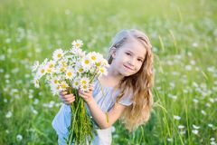 Cute little smiling girl in the chamomile field. In spring Royalty Free Stock Photography