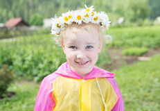 Cute little smiling girl in the chamomile wreath. And bright raincoat Stock Photos