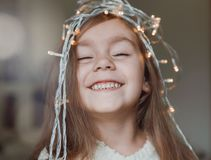 Cute little smiling girl with christmas luminous garland on her head. Christmas holiday portrait of happy child stock image