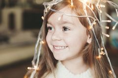 Cute little smiling girl with christmas luminous garland on her head. Christmas holiday portrait of happy child stock photos