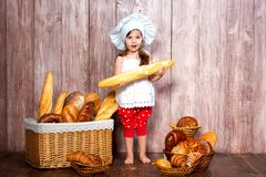 Cute little smiling girl in a cook cap stands near a wicker basket with bread rolls and bakery products.  royalty free stock images