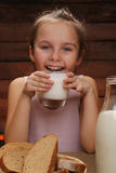 Cute little smiling girl is holding a glass of milk Royalty Free Stock Photography