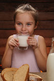 Cute little smiling girl is holding a glass of milk Stock Photo