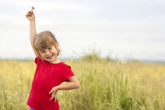 Cute little smiling girl holding little flower up in hand. Cute little smiling girl holding  flower up in hand Royalty Free Stock Images