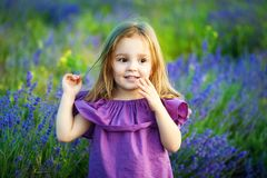 Cute little smiling girl in lavender field. Little blond child girl. concept of motherhood, protection of children. Beautiful girl playing in blooming lavender Royalty Free Stock Photography
