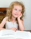 Cute little smiling girl reading Royalty Free Stock Images