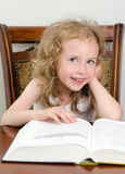Cute little smiling girl reading Stock Images