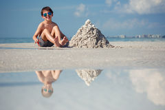 Cute little son building sand castle at beach Royalty Free Stock Image