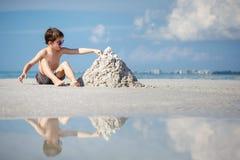 Cute little son building sand castle at beach in Florida Stock Photos