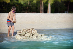 Cute little son building stone castle at beach Stock Photography