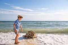 Cute little son building stone castle at beach Stock Photo