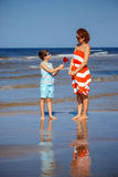 Cute little son giving present to his mother during beach vacation Stock Image