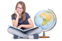 Cute little student girl with globe and book. Girl witrh glasses and teeth braces. School Education Concept Stock Photography
