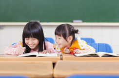 Cute little student look her classmate homework. In a classroom royalty free stock image