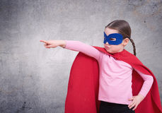 Cute little super hero girl in the red cloak against the gray wall Stock Images