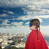 Cute little super hero girl in the red cloak against the urban background Stock Photos