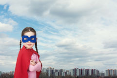 Cute little super hero girl in the red cloak against the urban background Stock Photo