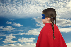 Cute little super hero girl in the red cloak. Superhero concept royalty free stock images