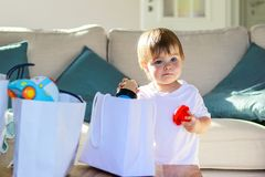 Cute little thoughtful baby boy with funny face expression taking out toys from shopping bags. At home. Child consumerism. Receiving gifts royalty free stock images