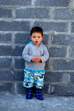 A Cute Little Toddler!. A cute little boy standing in front of a brick wall royalty free stock photos