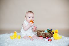 Cute little toddler baby boy, playing with colorful easter eggs. And little decorative ducks,  shot, beige background Royalty Free Stock Image